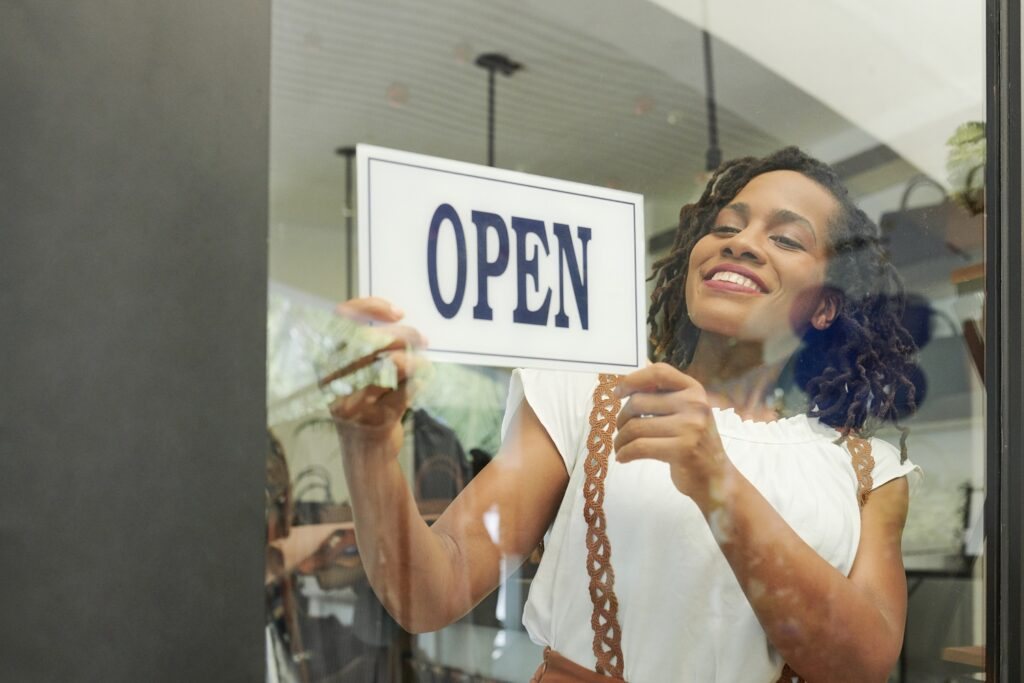 credit card processing fees: Smiling woman hanging an open sign in front of the store