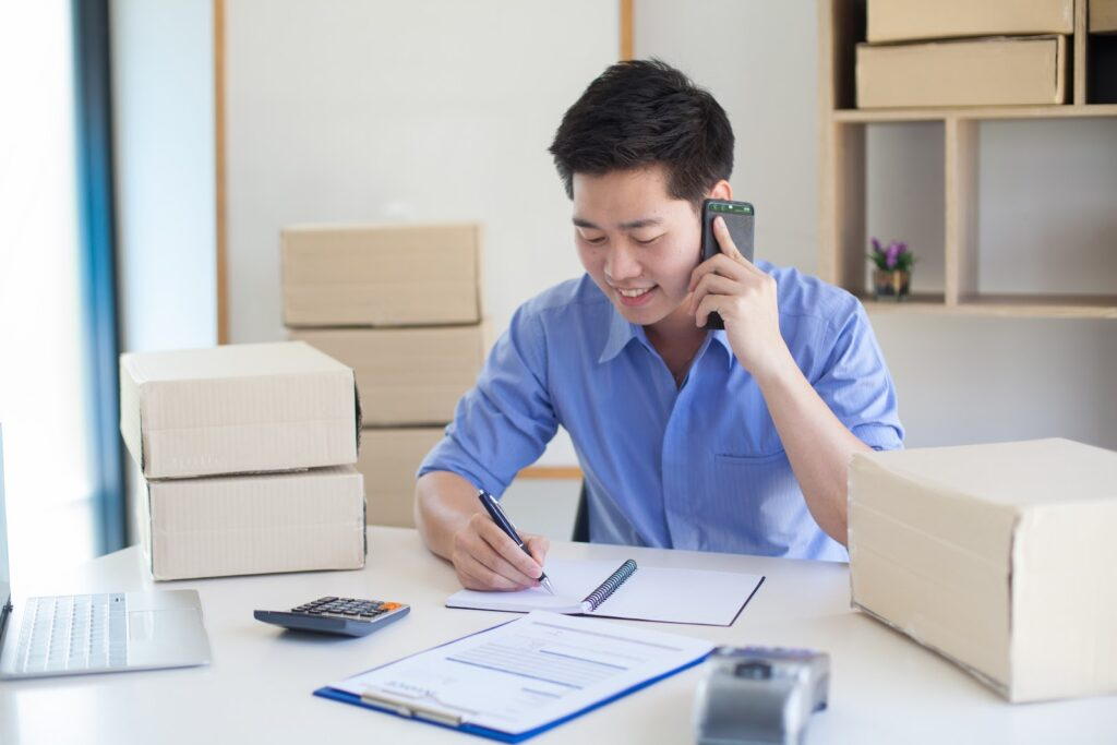 A business owner takes notes while on the phone