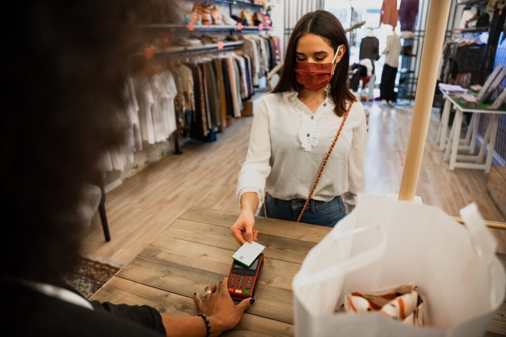 Credit card machine: A woman pays at a clothing store with a credit card