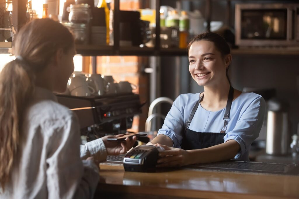 A customer uses contactless payment at a coffee shop