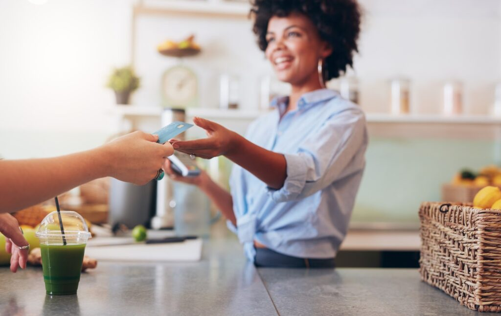EMV compliance: A woman at a juice bar accepts a credit card for payment