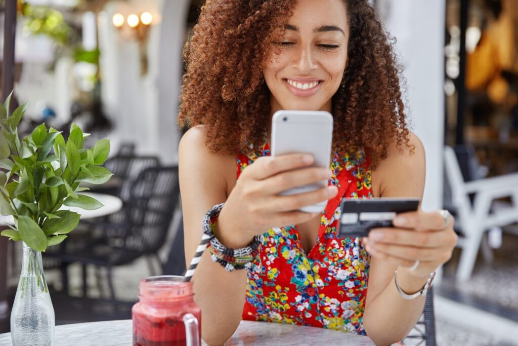How to accept credit card payments online: A woman makes a purchase on her cellphone while sitting in a cafe