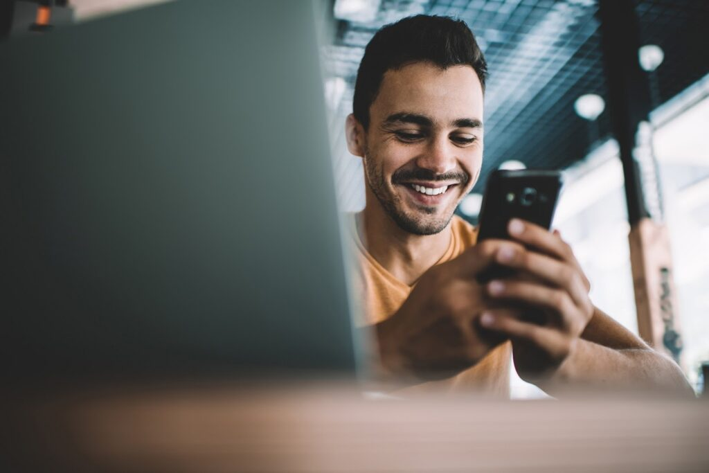 A smiling man looks at his cellphone