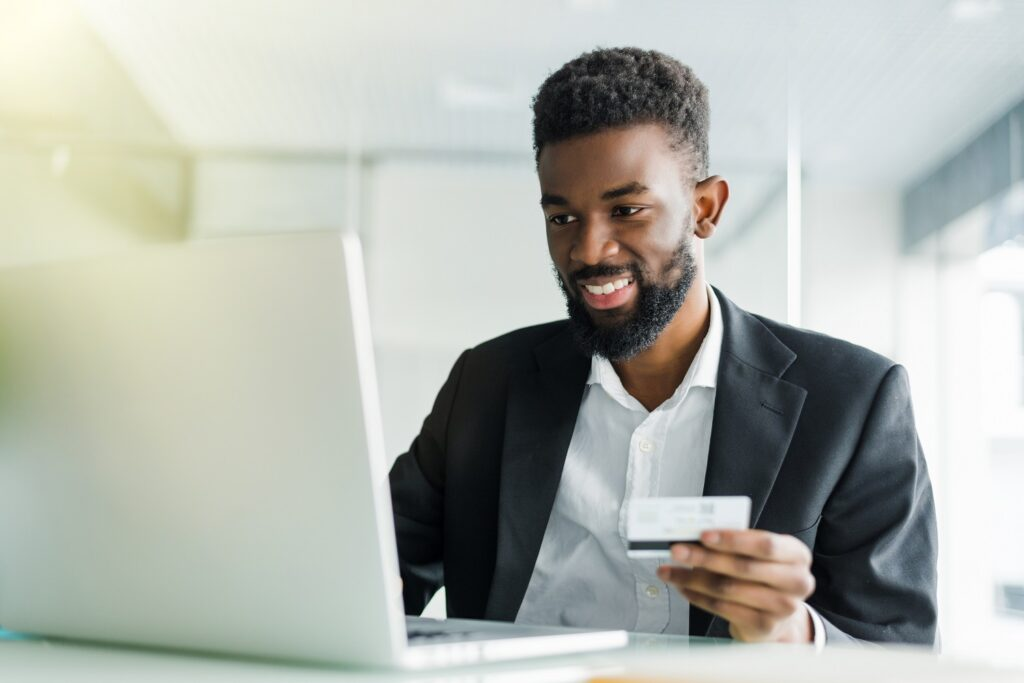how to accept credit card payments: Smiling man looking at his laptop while holding his credit card