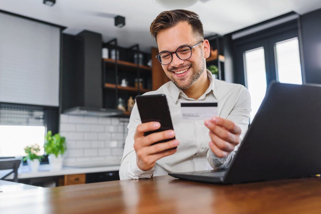 secure payment: man holding a phone and a credit card