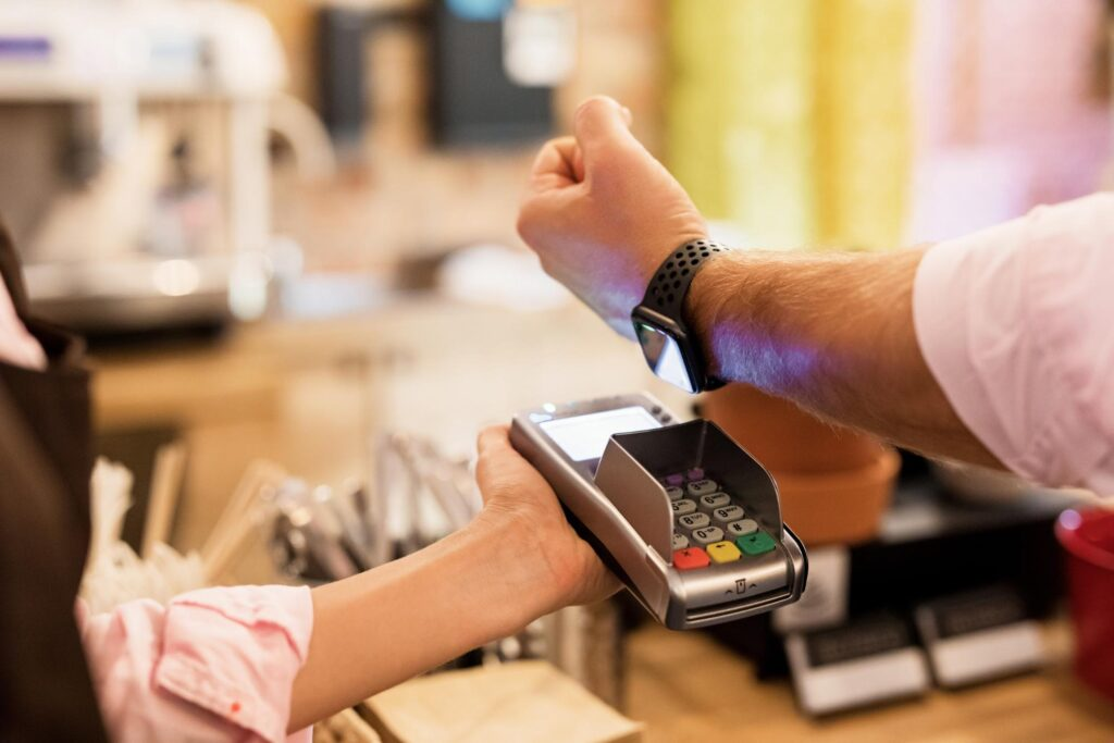 digital payment: Person paying at the cashier with a smartwatch on POS terminal