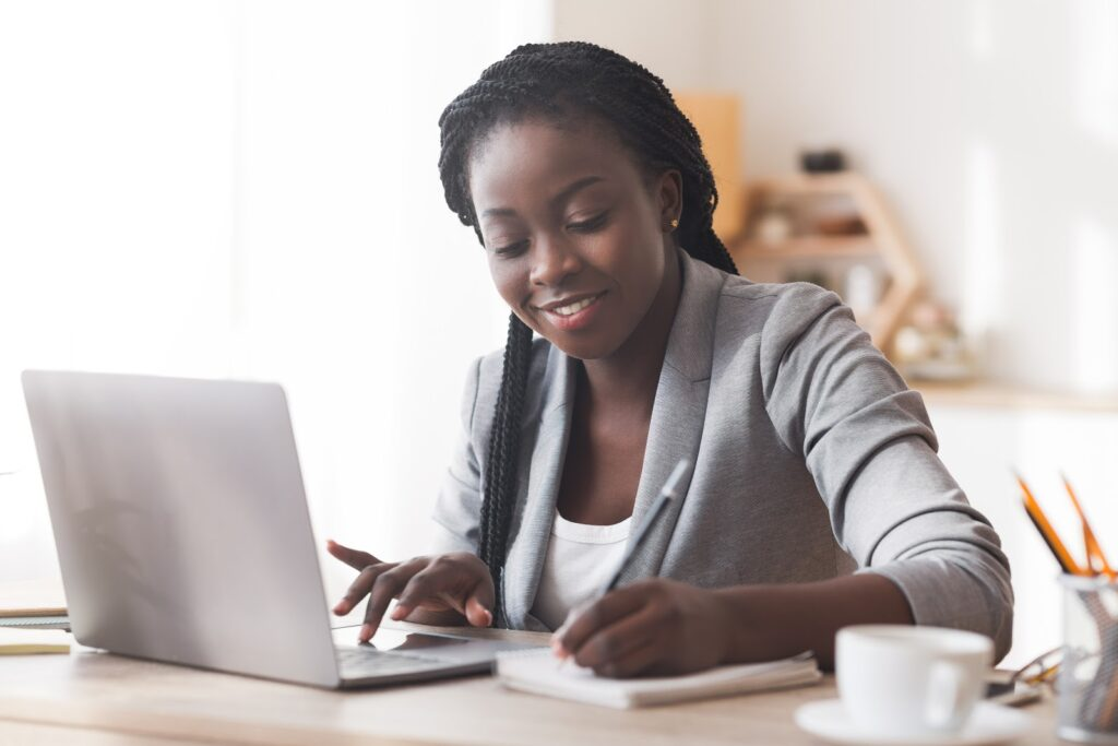 Small business credit card processing: A smiling woman takes notes while using her laptop