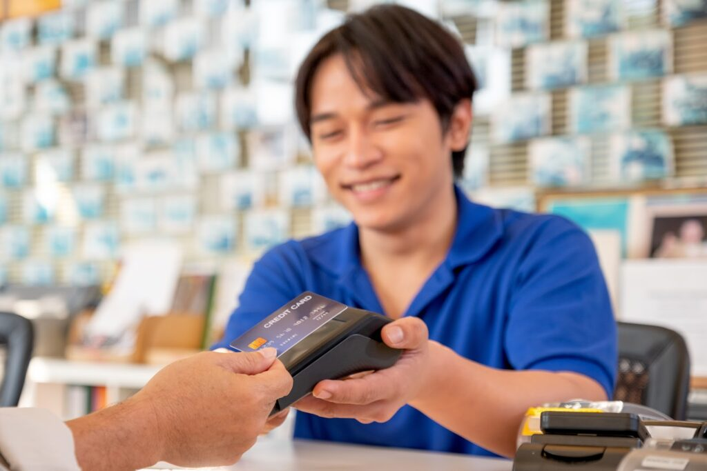A smiling business owner take a contactless credit card payment