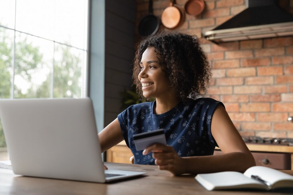 woman smiling while holding her credit card in front of her laptop
