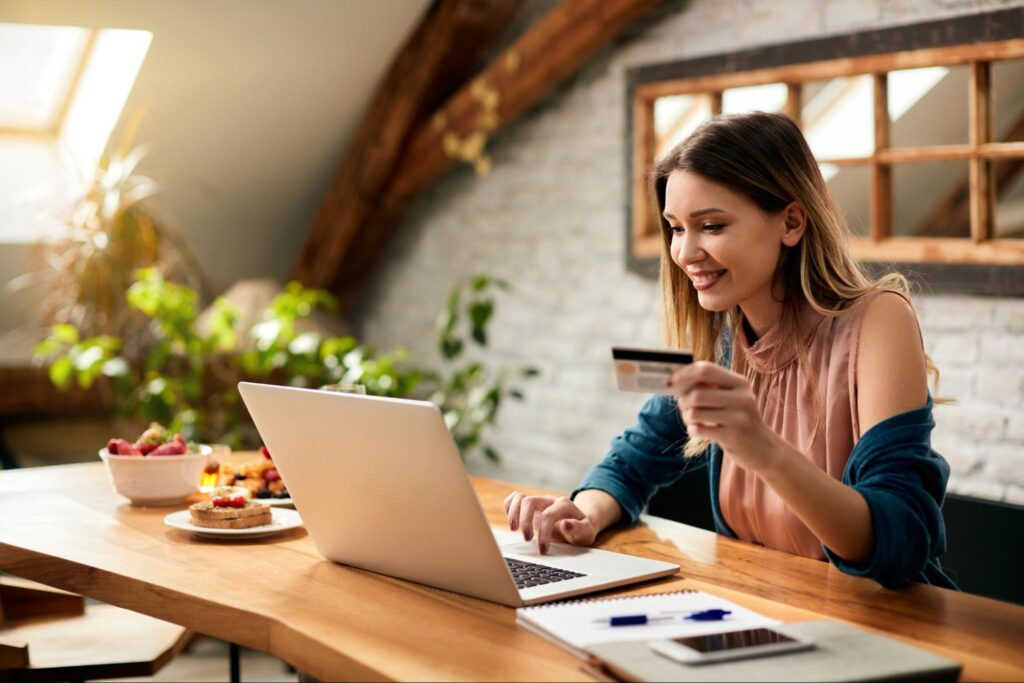 electronic payments: woman using her laptop while holding a credit card